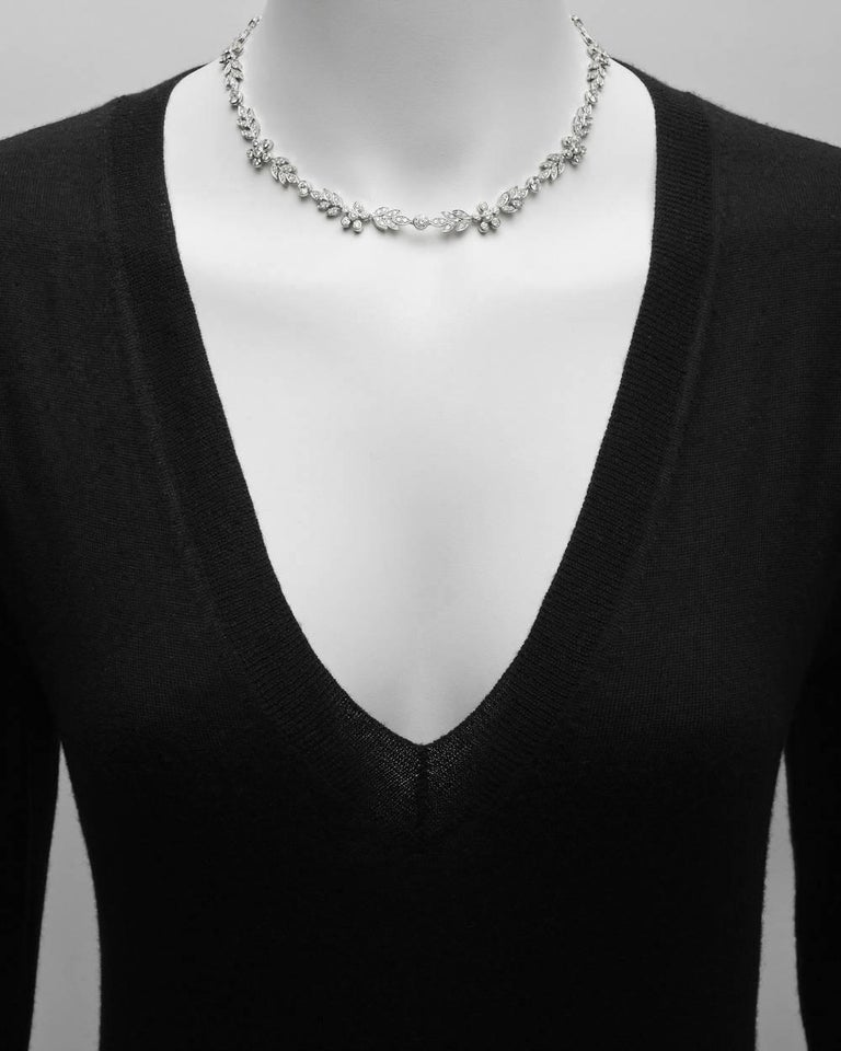 Diamond collar necklace, showcasing a variety of diamond-set floral motifs, in platinum. Near-colorless round brilliant-cut diamonds weighing approximately 8.35 total carats (H-color, SI-clarity, or better). 16