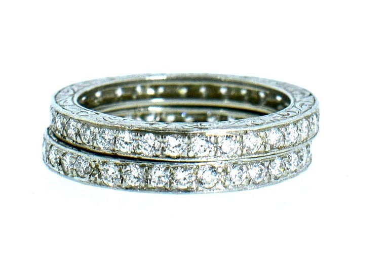 Eternity diamond bands in platinum set with 66 fine white, well cut, round brilliant cut diamonds amounting to approximately 1.65 cts.  These matching eternity bands are highly engraved, they are a size 6 and weigh 7.2 grams.  In new condition by