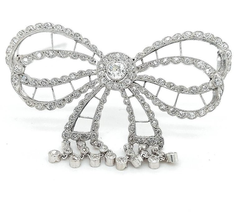 Stunning Platinum Artdeco Bowknot Diamond Brooch With Dangling Diamonds  Extremely fine handcrafted piece of art to make you shine on every occasion.  Hallmarks : French Eagle and numbered 3971  Diamonds: 144 diamonds + center diamond  Material: