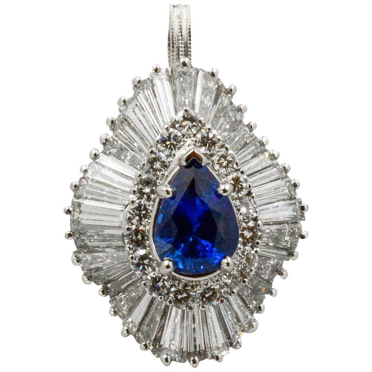This Circa 1970s Platinum ballerina ring features a 2.04 carat pear shape Ceylon Blue Sapphire. The ring has a detachable shank and a hidden bail that converts the piece into a pendant. It's surrounded by 17 round brilliant cut diamonds and 36
