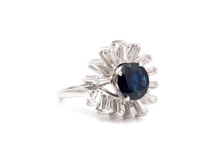 Fashionable and modern designed platinum baguette diamond and 2.63 carat round deep blue sapphire ring. 14 vibrant baguette diamonds have an approximate total weight of 1.25 carats with approximately F color, VS2 clarity. Round blue sapphire has