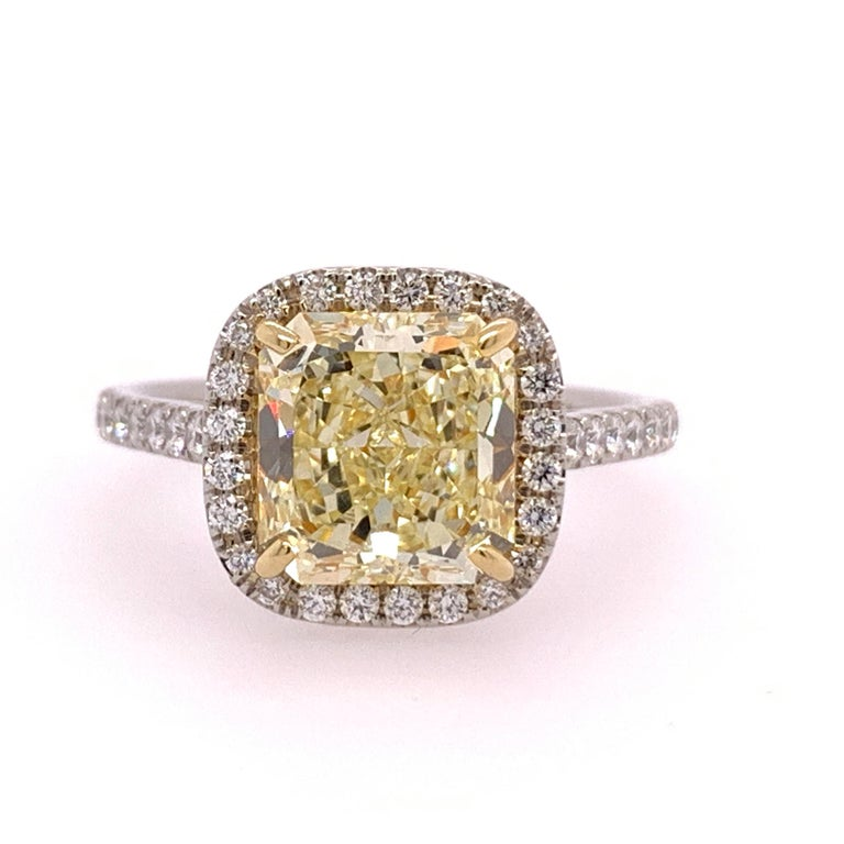 Platinum ring set with 46 Natural colorless round brilliant diamonds weighing a total of 0.40 carats. The ring size is a 6.  The centerstone is an exquisite Natural Fancy Yellow, VVS1 clarity and No Fluorescence.