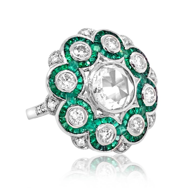 This stunning and captivating emerald and diamond ring is crafted in solid platinum, centered with a rose cut diamond graded G-H/I1, enhanced with other 20 round diamonds, majority graded G-H/SI, few VS. The total diamonds weigh approx. 1.75ct. The