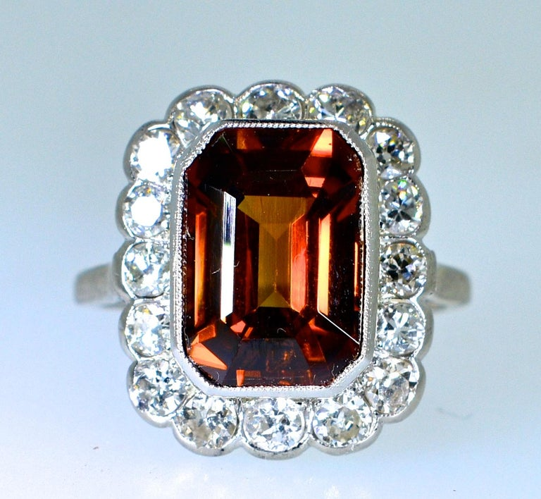 The center stone is a fine natural Zircon.  The tawny color is very unusual.  It's chestnut like color has flashes of red which one rarely sees.  This stone weighs approximately 10 cts. and is surrounded by fine white old cut diamonds.  The diamonds