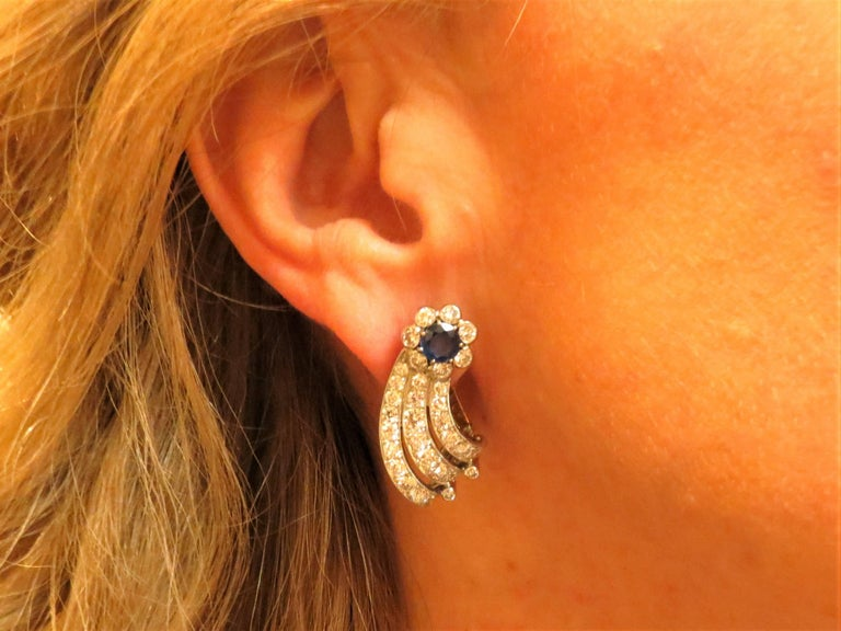 Platinum  ear clips prong set with two round faceted blue sapphires weighing 1.30cts and 64 full cut round diamonds weighing 3.50cts, G-H color, VS clarity, with 14K yellow gold clip back.