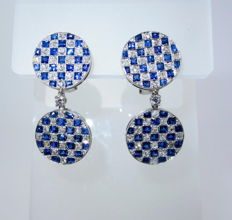 Sapphire, diamond and platinum checkerboard motif earrings, pendant style, which are 1.25 inches long and possessing fine white diamonds and bright blue natural square cut sapphire.  There are 94 round white diamonds weighing approximately 2.65