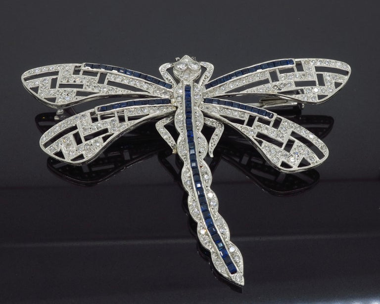 Vintage diamond and blue sapphire dragon fly brooch crafted in platinum.  Gemstone: Diamond and Blue Sapphires Gemstone Carat Weight: 76 Approximately 1.5mm Blue Sapphires Diamond Cut: Single Cut Diamonds Average Diamond Color: G-K Average Diamond