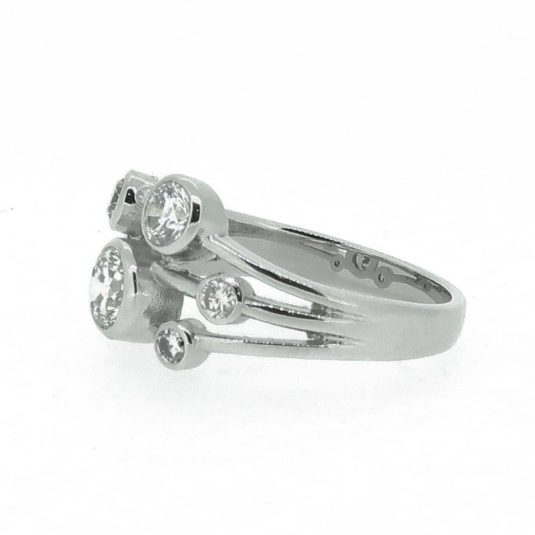 Platinum Diamond Bubble Cluster Ring   A dazzling diamond bubble cluster ring. Consisting of seven brilliant cut diamonds, randomly set over three platinum bands. the three gold bands taper down to form one thicker shanks. All stones encased in a
