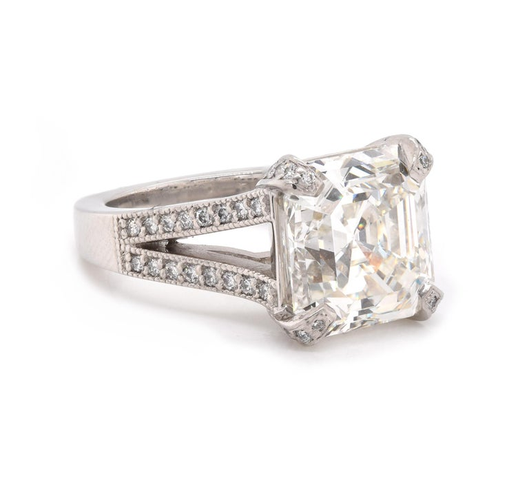 Designer: custom Material: Platinum Center Diamond: 1 square emerald cut = 7.52ct Color: J Clarity: VS2 GIA: 215623507 Diamond: 32 round cut = .32cttw Color: H Clarity: VS1 Ring Size: 6.5 (please allow up to 2 additional business days for sizing