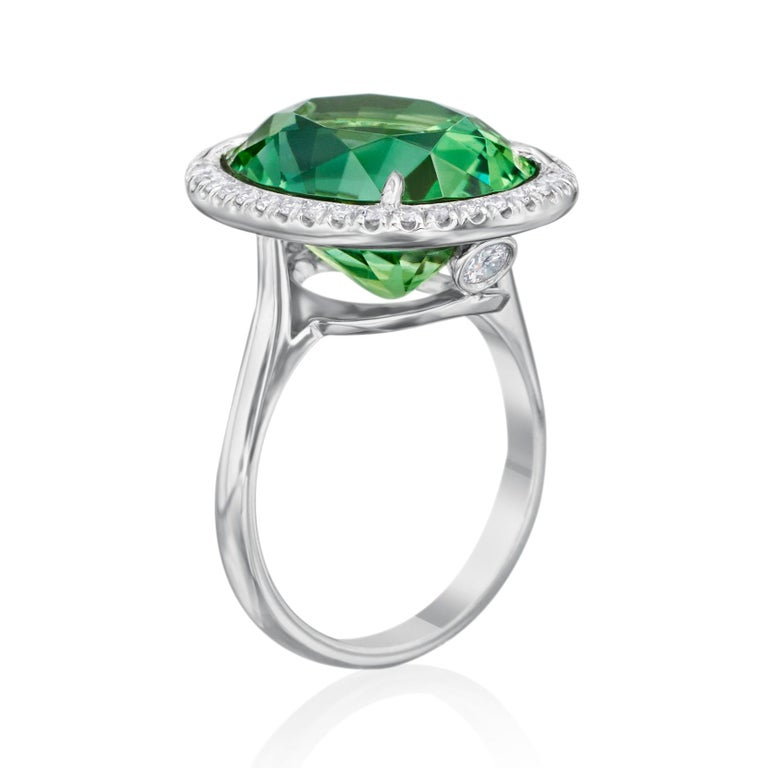Complement her daring and lovely personality with the breathtaking color and classic halo design of this remarkable gemstone and diamond ring. Stunning in platinum, this extraordinary 10.55 carat oval faceted green Tourmaline is surrounded by 36