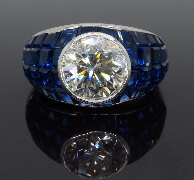 Vintage approximately 2.62CT Round Brilliant Cut diamond ring with blue sapphires set in a mosaic design crafted in platinum  Gemstone: Diamond and Sapphire Gemstone Size: Irregular Cut Blue Sapphires ranging from approximately 2.00-2.4mm in