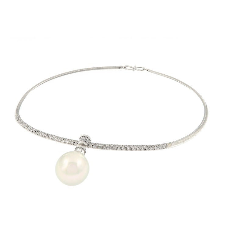 The beautiful platinum domed Omega chain is accented with pave set diamonds and features a white South Sea cultured pearl pendant. Pearl pendant is detachable and is capped with baguette diamonds. This estate necklace is 15.5 inches long and in
