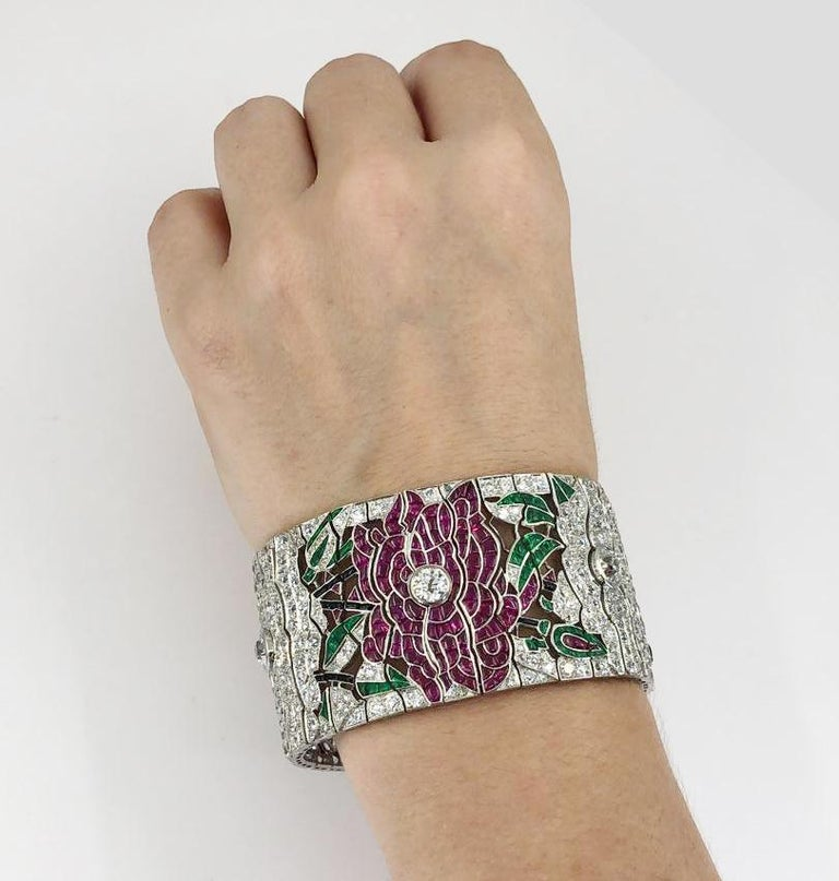 Platinum Diamond, Ruby, Emerald & Onyx Flower Wide Bracelet.  Diamond weight is approx. 22.50 carats total. Ruby weight approx. 36.14 carats total. Emerald weight approx. 7.45 carats total. Measures approx. 1.37″ in width by 7.25″ in length, with an