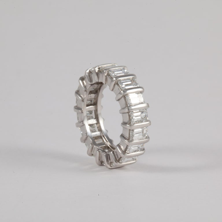 Set in platinum, this eternity band holds eighteen (18) emerald cut diamonds weighing 7.0 carats; they are E-G in color and VVS-VS in clarity.  There are platinum bars between each diamond making this ring heavy and durable.  Measures 1/4