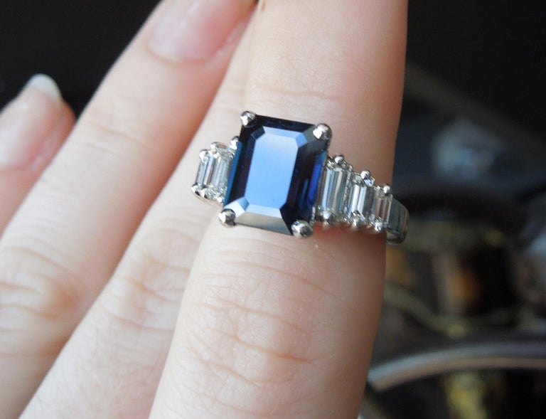 Featuring a central 4 carat Emerald cut Blue Sapphire, with a slight Green tinge, at 9.5mm in length x 7.5mm in width, secured in a 4-Prong setting. With a total of approximately 0.90 carats of Colorless Nearly Flawless Rectangular Baguette cut