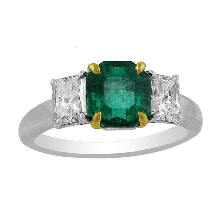 A beautiful estate platinum ring with a center 1.85ct emerald, prong-set in 18k yellow gold, and two prong-set side diamonds weighing a total of 1.2cttw. GIA Certified emerald, F2 clarity enhanced.  All information provided for your trust and