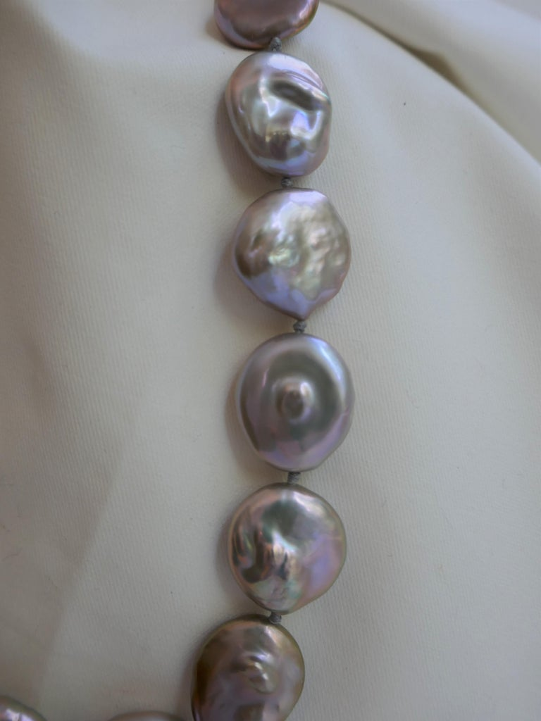 This cultured pearl necklace is stunning given the size of the coin keshi pearls (18-20mm x 22-25mm) and their color. This is a statement necklace. The platinum grey coin keshi pearls have beautiful tones and luster and goes with everything The