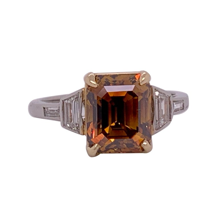 A rare Deep Orange-Brown Emerald Cut weighing 3.37 carat and certified by the GIA as an SI1 in clarity. Pleasant rectangular shape and extraordinary color. Ring is a size 6.25. The platinum ring contains approximately 0.35cts.
