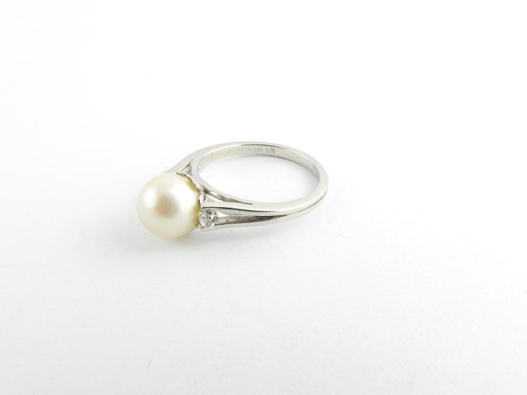 Vintage Platinum Pearl and Diamond Ring Size 5.5  This elegant ring features on cultured pearl 8 mm and two round brilliant cut diamonds set in classic platinum. Shank: 2 mm.  Approximate total diamond weight: .04 ct.  Diamond color: G  Diamond