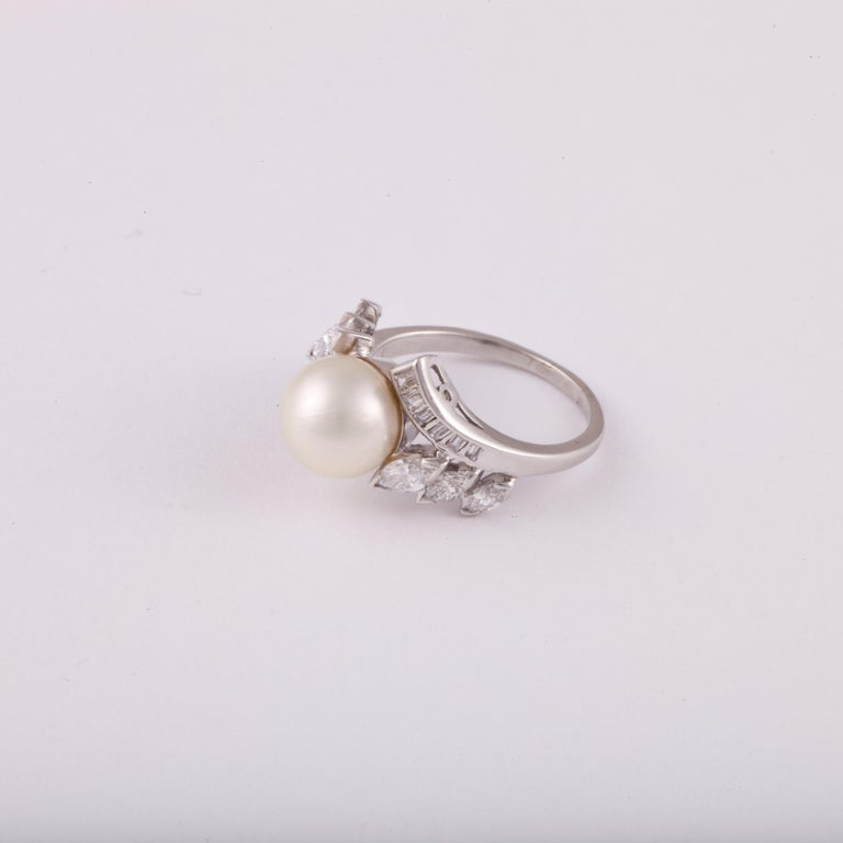 Platinum ring set with a cultured pearl in the center; the pearl measures 9.25mm.  There are marquise and baguette diamonds down the shank which total 1.05 carats; they are F-G in color and VS in clarity.  Ring is currently a size 6-3/4.