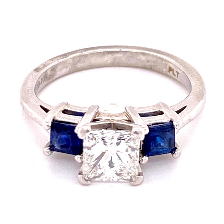 Beautiful three stone diamond and sapphire ring is handcrafted in platinum. The 1.02 princess cut diamond is GIA certified and graded G color and VS2 clarity. The center diamond is set between two beautiful blue princess cut natural sapphires