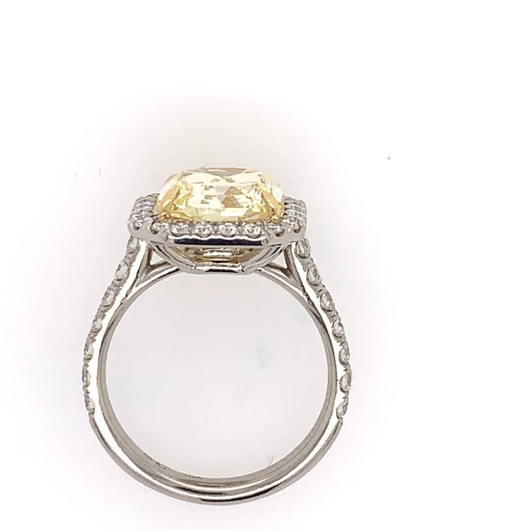 Platinum and 18K Yellow Gold Canary Ring. The centerstone is a Radiant Cut 4.05ct GIA certified as a Natural Fancy Yellow Diamond , Internally Flawless. No Florescence.   The ring is set with 38 natural colorless round brilliant diamonds weighing