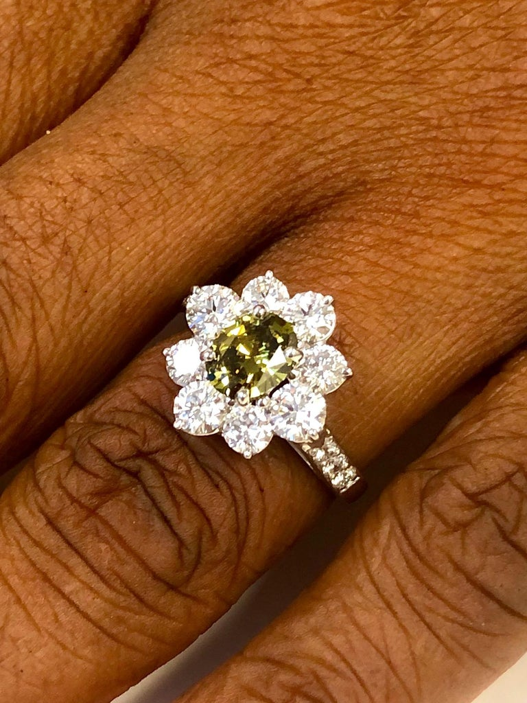 Natural Color Oval Diamond 0.72 carats, with very unusual Green tones set in a Platinum Ring surrounded by 14 fine white round diamonds 1.68 carats.  We design and manufacture all our jewelry in our workshop, located in New York City's diamond