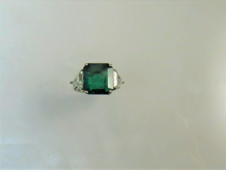 Platinum ring prong, set with one Columbian emerald cut emerald weighing 6.98cts and two prong set triangular cut diamonds weighing 1.50cts, GH color, SI clarity. Finger size 6.5. May be sized Retail $95000