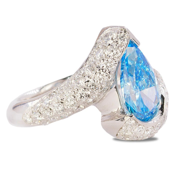 Platiunm Ring with GIA certified HPHT Fancy Vivid Blue, VVS2 Pear Shape DIamond and 2.71 carats of pave set modern round brilliant diamonds.