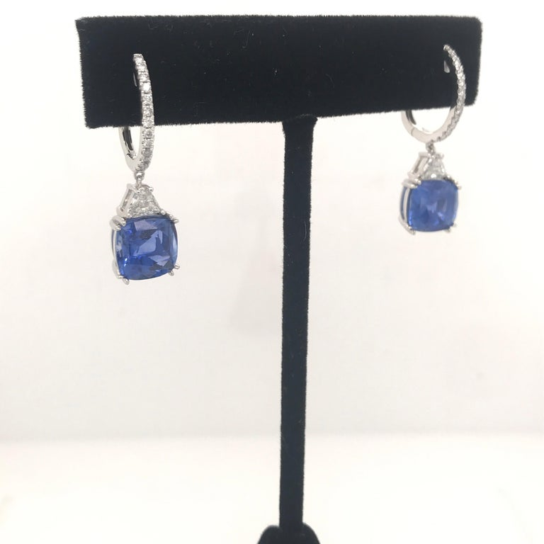 Platinum drop earrings featuring two blue sapphires weighing 8.01 carats, 2 trapezoids weighing 0.45 carats and 26 round brilliants weighing 0.25 carats.