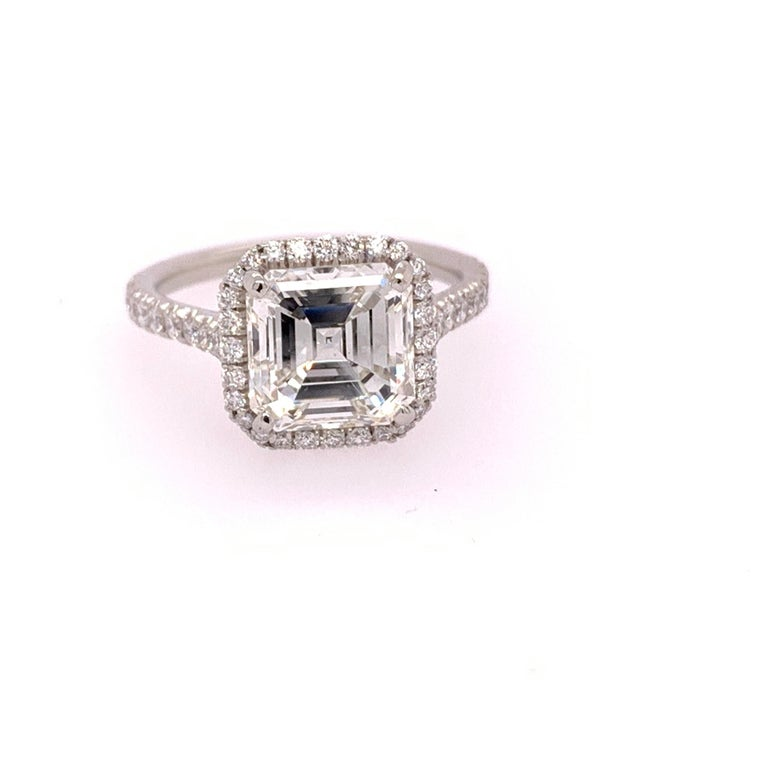 Platinum Ring (size 4) set with 46 colorless natural round brilliant diamonds weighing 0.35 carats. Ring can be sized.  The center is gemstone, a 2.57ct square emerald cut GIA I in color and vs2 in clarity, no florescence. It measures 7.7mm.   Total