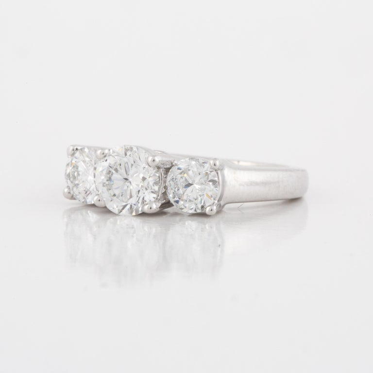 Three stone ring set in platinum.  The center diamond is GIA certified (Report 6207160225).  It is 1.01 carats with D color and SI2 clarity.  The two side diamonds total 0.97 carats; F-G color and SI1-SI2 clarity.  Measures 5/8