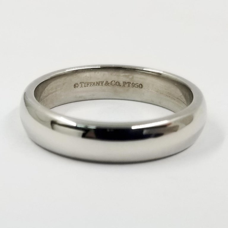 This simple half round wedding band from Tiffany & Co is crafted in platinum with a high polish shine. The interior is stamped PT950. Width is approximately 4.5 millimeters. Current finger size is 7.75; purchase includes free sizing (up or down 1
