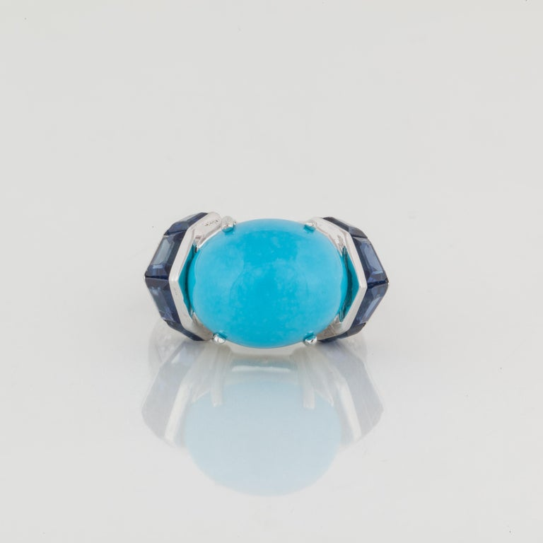 Beautifully designed ring set in platinum.  The center stone is a cabochon turquoise. On each side are calibre cut sapphires and down the shank are diamonds.  There are twelve (12) round diamonds, as well as six (6) baguettes with a total carat