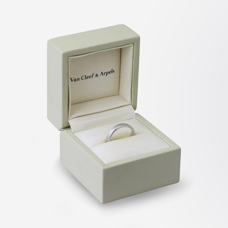 A brushed platinum band in its original retailing box by Van Cleef & Arpels. The ring is hallmarked internally with Van Cleef & Arpels markings and serial number, and a French purity mark and secondary makers mark to the outside of the shank (band).