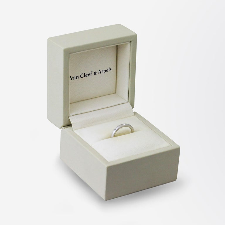 A brushed platinum band set with three diamonds by Van Cleef & Arpels. This particular ring is titled 'Infini Etoile' and is presented in its original leather retailing box. The piece is set with three brilliant cut diamonds and is fully signed to