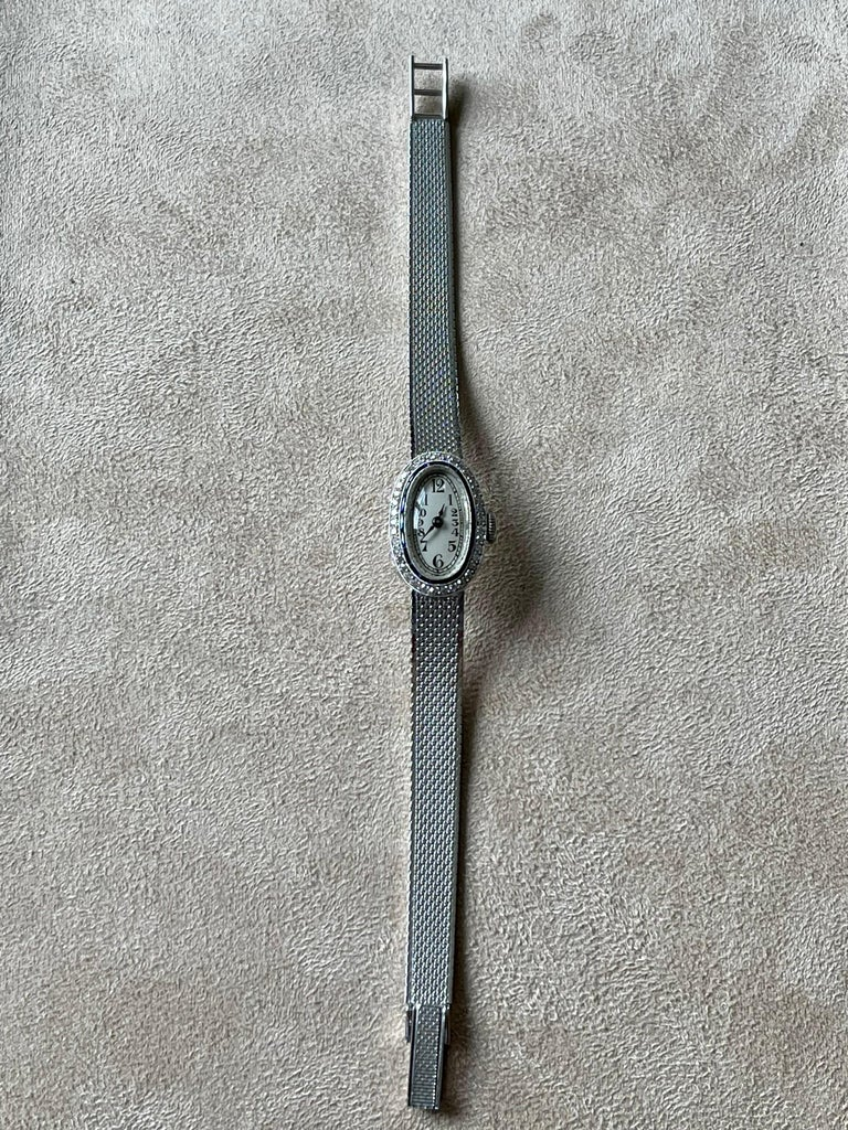 This stunning and very elegant oval 1920 Art Deco wrist watch features a platinum  with blue Sappires and Diamonds case along with the dial's stylized numerals. The white gold mesh band is smooth, sleek and has an adjustable buckle to accommodate