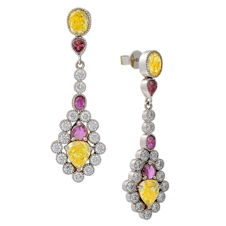 These amazing colorful diamond dangle earrings feature yellow, purple, and white natural diamonds. The 4.13 carats of natural fancy yellow and natural fancy light yellow diamonds all have GIA certificates. There are another 1.36 carats of natural