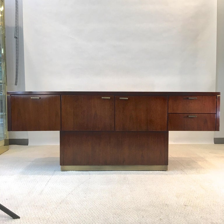 Warren Platner style 1970s architectural floating sideboard in walnut with bronze hardware and plinth base. Finished on all sides so it can be placed anywhere in a room.  First door is actually a deep file hanging drawer. Middle two doors open to