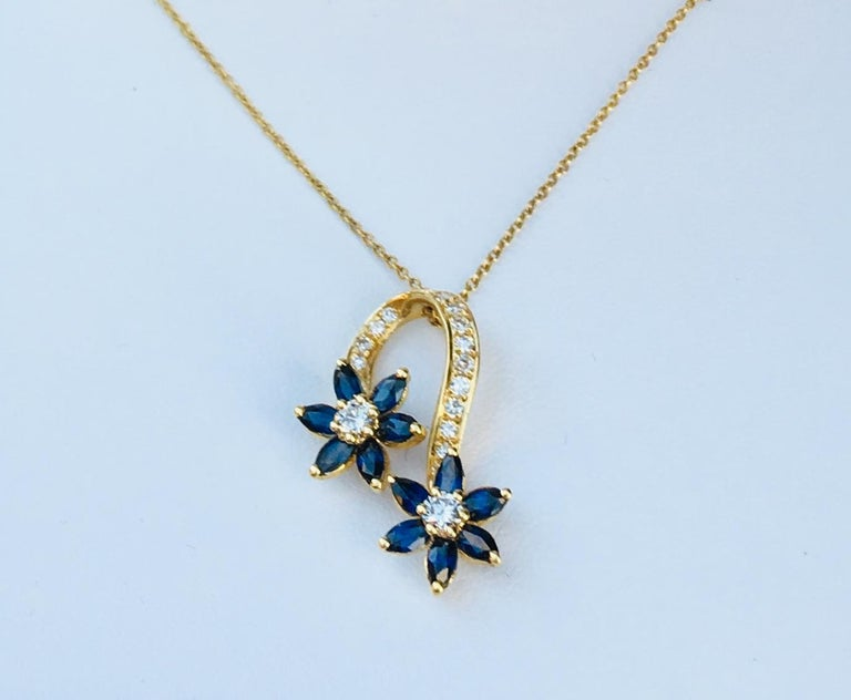 Elegant and stylized estate 18 karat yellow gold pendant on chain features two spinning flowers with prong set round brilliant diamond centers and 6 prong set, marquise cut blue sapphire petals.  Flowers are connected by a graceful 18 karat yellow