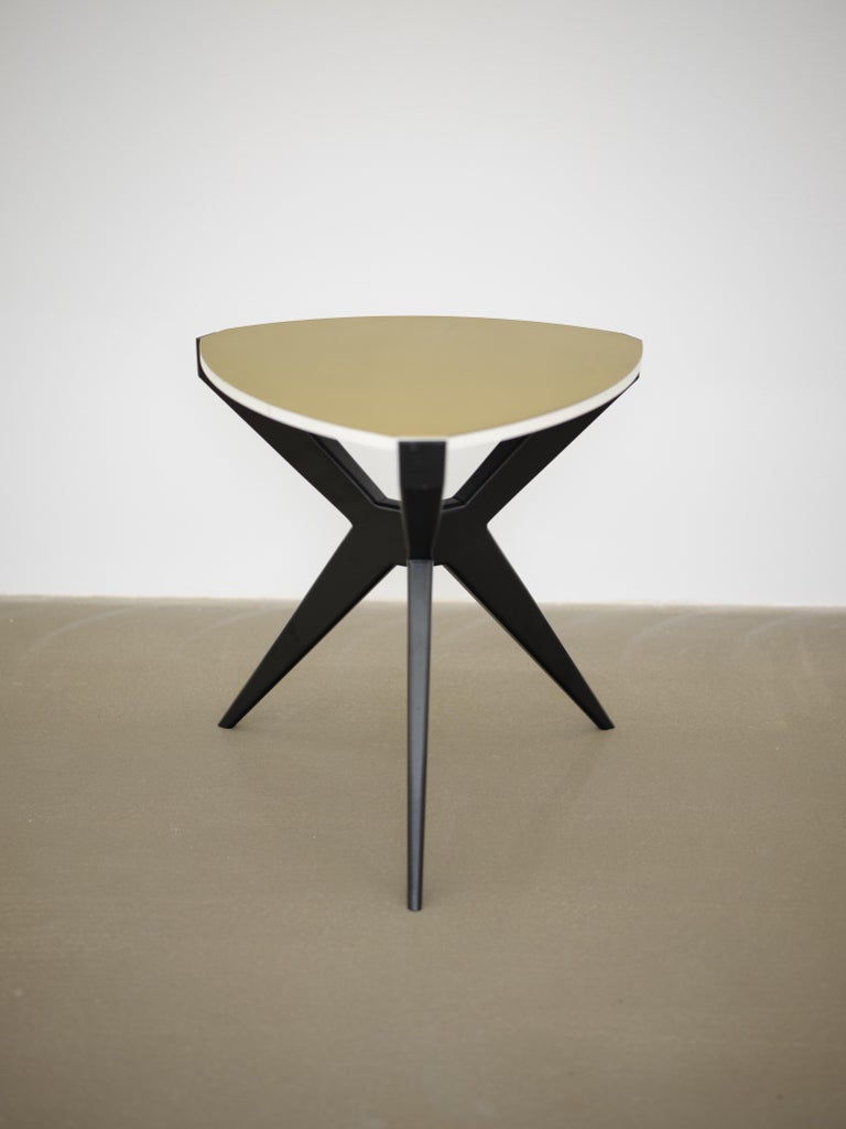 Plettro is a contemporary side table. This version has black laqueered legs and a brushed brass top. It's named after the guitar plectrum shape of the stone. Plettro side table has Sputnik legs that accommodate the stone top like a gem mounted on a