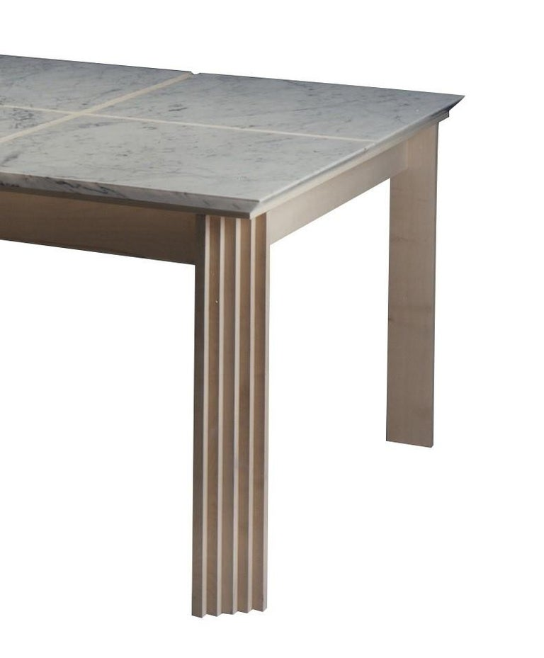 Part of the Plinto series, this table features a square top that is made of four elements in white Carrara marble rich in natural veins. The top can also be in travertino marble. Legs are in maple wood, but also available are Italian walnut wood,