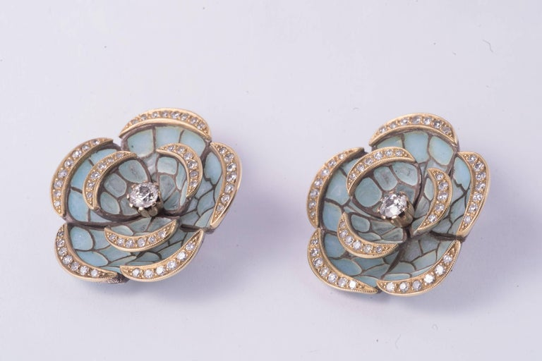 Luminous light blue Plique-à-Jour flower earrings with 50 single cut diamonds and a .30ct round european cut diamond in the center in each earring all having G-H color and VS-SI clarity. The total diamond weight is approx. 3.10cts.
