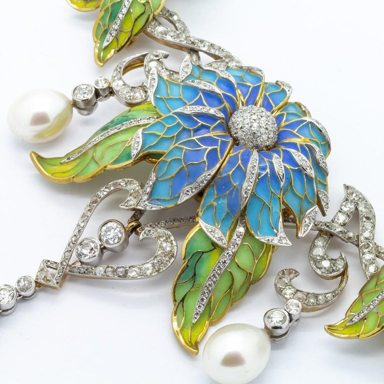 A Moira Collection, plique-à-jour enamel flower necklace. The necklace, has sky blue plique-à-jour enamel flowers, and green plique-à-jour leaves, with old-cut and eight-cut diamonds and three large cultured drop pearls at the front, mounted in