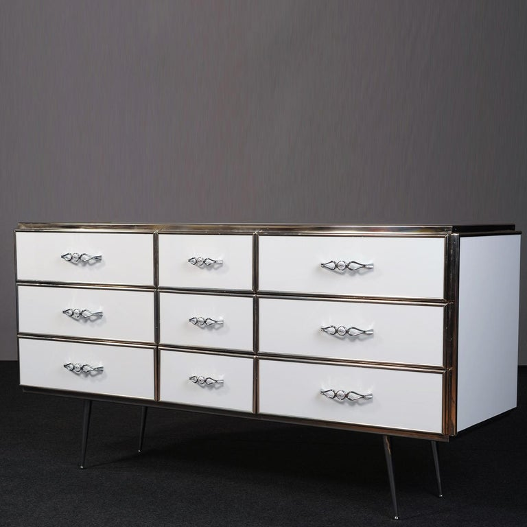 Covered with glossy white acrylic film, this wooden dresser boasts vintage-style profiles, stiletto legs, and handles sure to infuse their refined charm into any bedroom decor. The storage unit is organized into three vertical rows each with three