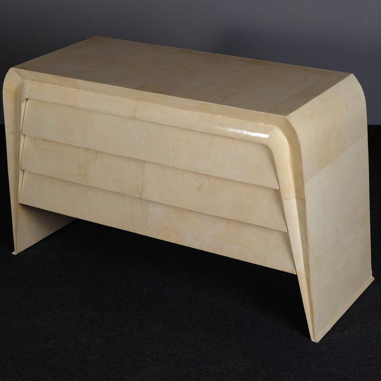 The dynamic lines and glamorous character distinguishing Art Deco-inspired designs is impeccably exemplified in this precious dresser. Fully upholstered with top-quality natural parchment, the piece is sure to make an uplifting statement in any