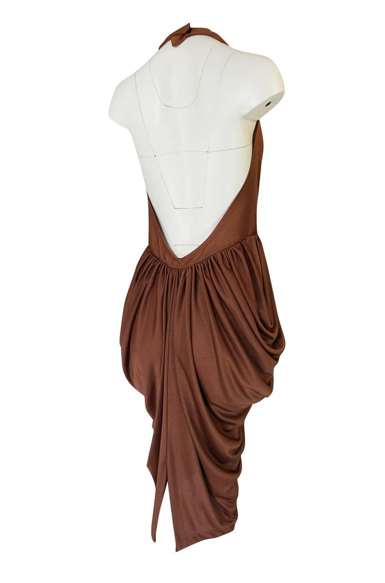 This dress is amazing. It is insanely sexy with a halter style front that plunges to just above the waist and has a back that is left completely open and bare. It is made of a liquid jersey in a deep taupe brown that feels amazing on. That fabric