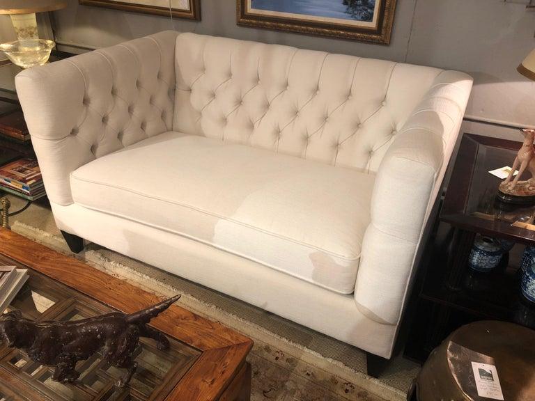 A glamorous tufted loveseat having a box shape, removable single seat cushion and ebonized feet. Measurers: Seat height 19 seat depth 26.5.