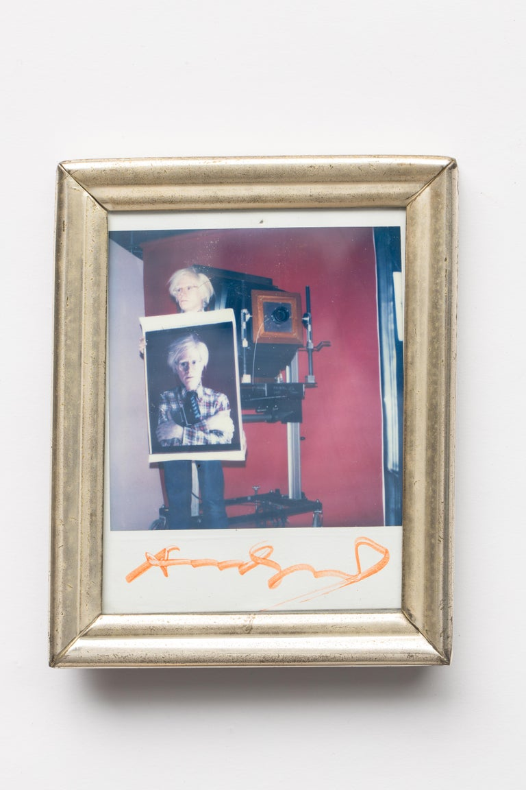 Bill Ray (1936-2020) polaroid photo of Andy Warhol holding a self-polaroid with 20 x 24 polaroid camera in background, circa 1980. The photo Andy is holding was minutes old, shot by Bill Ray for New York magazine with the 20 x 24 camera in