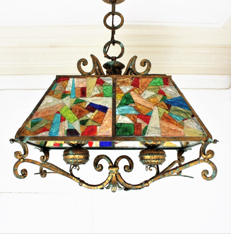 A massive multi-color hammered glass and gilt wrought iron suspension lamp. Manufactured by Longobard, the concurrent of Poliarte at the 1960s. This ginormous lantern in Brutalist style has classical accents. The structure is made in heavy wrought